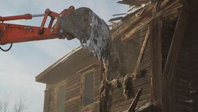 Close-up bucket destroys the old wooden building. Car Demolition stock video