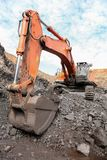 Close up of the scoop of an excavator digging ore rocks. Close up of the bucket of excavator digging and loading ore rocks at a Manganese mine stock photography