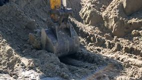 Close-up of a bucket excavator raises the ground. Concept of construction. Close-up of a bucket excavator raises the ground. Concept of construction stock footage