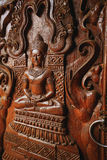 Close up buddha carved wooden texture of a door in thai temple. Stock Photos