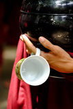 Close up of buddhist monk hands holding a vintage bowl and cup Royalty Free Stock Photography