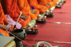 Close up of Buddhist monk prepare to pouring melt candle tears to the water for making blessing water. Close up at Monk hands for prayer and religious rituals stock images