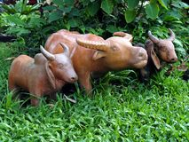 Close up buffalo and cow baked clay doll standing on green grass field amidst freshness lush bush. Buffalo and cow baked clay doll standing on green grass field stock photography