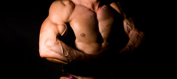 Close-up build muscle bodybuilder. On a dark background Royalty Free Stock Image