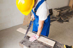 Close up of builder with arm saw sawing board. Building, carpentry, repair, teamwork and people concept - close up of builder with arm saw sawing board on table Stock Photo