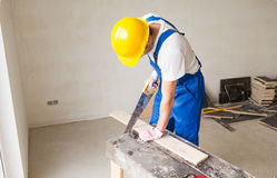 Close up of builder with arm saw sawing board. Building, carpentry, repair, teamwork and people concept - close up of builder with arm saw sawing board on table Royalty Free Stock Image