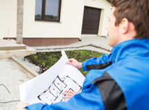 Close up of builder with blueprint over house Stock Images