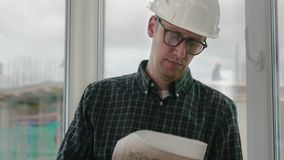 Builder engineer wear security helmet look at blueprint paper construction drawing plan on background of window frame. Close up.Builder engineer wear security stock video