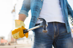 Close up of builder hand in glove holding hammer Royalty Free Stock Photo