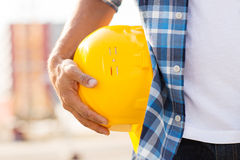 Close up of builder hand holding hardhat outdoors Royalty Free Stock Images