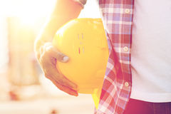 Close up of builder hand holding hardhat outdoors. Building, construction, protective gear and people concept - close up of builder hand holding yellow hardhat Stock Image