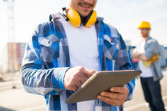 Close up of builder with headphones and tablet pc Stock Image