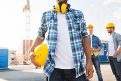 Close up of builder holding hardhat at building. Building, construction, protective gear and people concept - close up of builder holding yellow hardhat or Stock Image