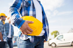 Close up of builder holding hardhat at building. Building, protective gear and people concept - close up of builder hand holding yellow hardhat or helmet at Royalty Free Stock Images