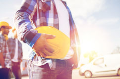 Close up of builder holding hardhat at building. Building, protective gear and people concept - close up of builder hand holding yellow hardhat or helmet at Stock Photography