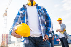 Close up of builder holding hardhat at building. Building, protective gear and people concept - close up of builder holding yellow hardhat or helmet at Stock Image