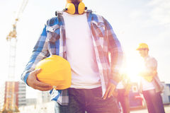 Close up of builder holding hardhat at building. Building, protective gear and people concept - close up of builder holding yellow hardhat or helmet at Stock Photo