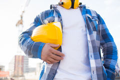 Close up of builder holding hardhat on building. Building, protective gear and people concept - close up of builder holding yellow hardhat or helmet outdoors at Stock Images