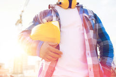 Close up of builder holding hardhat on building. Building, protective gear and people concept - close up of builder holding yellow hardhat or helmet outdoors at Royalty Free Stock Photography
