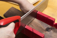 Close up of builders with arm saw sawing board. Building, carpentry, repair, teamwork and people concept – close up of builders with arm saw sawing board on Stock Photo