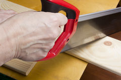 Close up of builders with arm saw sawing board Royalty Free Stock Photo