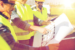 Close up of builders with blueprint at building Royalty Free Stock Photo