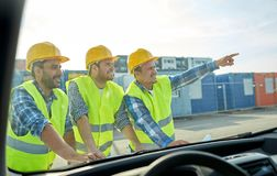 Close up of builders with blueprint on car hood Royalty Free Stock Images
