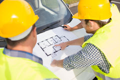 Close up of builders with blueprint on car hood Royalty Free Stock Image