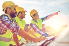 Close up of builders with blueprint on car hood. Building, construction, development, teamwork and people concept - close up of builders in hardhats and high Royalty Free Stock Image