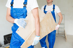 Close up of builders carrying wooden boards Stock Photo