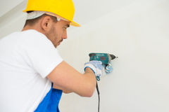 Close up of builders with drill perforating wall Royalty Free Stock Image