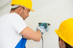 Close up of builders with drill perforating wall Stock Photos