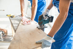 Close up of builders with electric saw and board Royalty Free Stock Images
