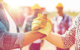 Close up of builders hands making handshake. Building, teamwork, partnership, gesture and people concept - close up of builders hands in gloves greeting each royalty free stock photos
