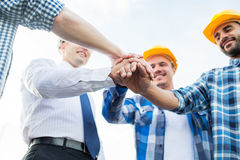 Close up of builders in hardhats with hands on top Royalty Free Stock Images