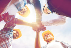 Close up of builders in hardhats with hands on top Stock Photo