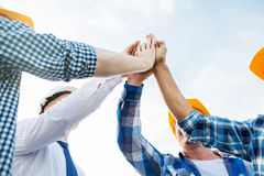 Close up of builders in hardhats making high five Stock Photo