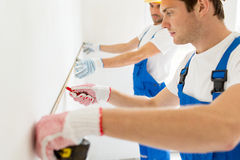 Close up of builders measuring wall with tape Stock Photography