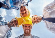 Close up of builders wearing hardhats in circle. Business, building, partnership, construction and people concept - close up of smiling builders and architect in stock photography