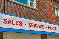 Close up of building exterior with a huge sign that reads Sales Service Parts. The old building has brick wall and the windows have white frames royalty free stock images