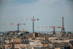 Close-up of buildings rooftops, cranes and Eiffel Tower on the horizon in Paris. royalty free stock image