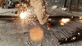 Close-up of the Bulgarian cuts metal in slow motion. Sparks fly out from under the wheel of the grinder in slow motion. 960fps stock footage
