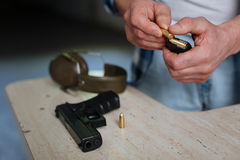 Close up of a bullet being put into the cartridge clip Stock Photos