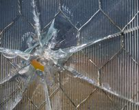 Bullet Hole in Wire Mesh Glass with Ridges. Close up of a bullet hole through wire mesh glass. The glass has ridges and the bullet hole caused rays of cracks in Royalty Free Stock Photo