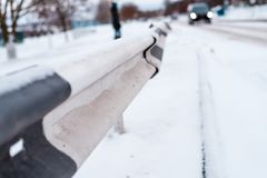 Close-up of the bump in winter on the road, in winter in the city the car is far away. Close-up of the bump in winter on road, in winter in the city the car is Royalty Free Stock Images