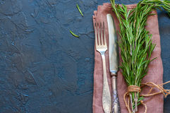 Close up of bunch of green fresh rosemary, knife and fork on a s Stock Photos