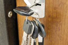 Close-up of bundle of different keys in key hole in wooden textu Stock Photos