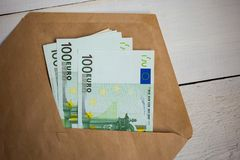close up bundle of money Euros banknotes in envelope on wooden table stock photography