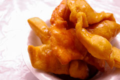 Close up of bunuelos served on a white plastic plate doused in honey Royalty Free Stock Photography