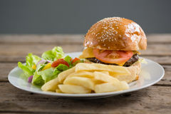Close up of burger and french fries with vegetables Royalty Free Stock Photo